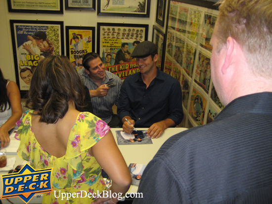 Tony chuckles while talking with reporter Jon Gold about the event while he signs photos for the members.
